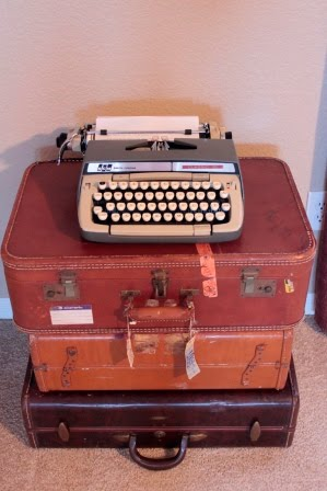 Vintage typewriter on a stack of vintage suitcases. Very cute, but everywhere.